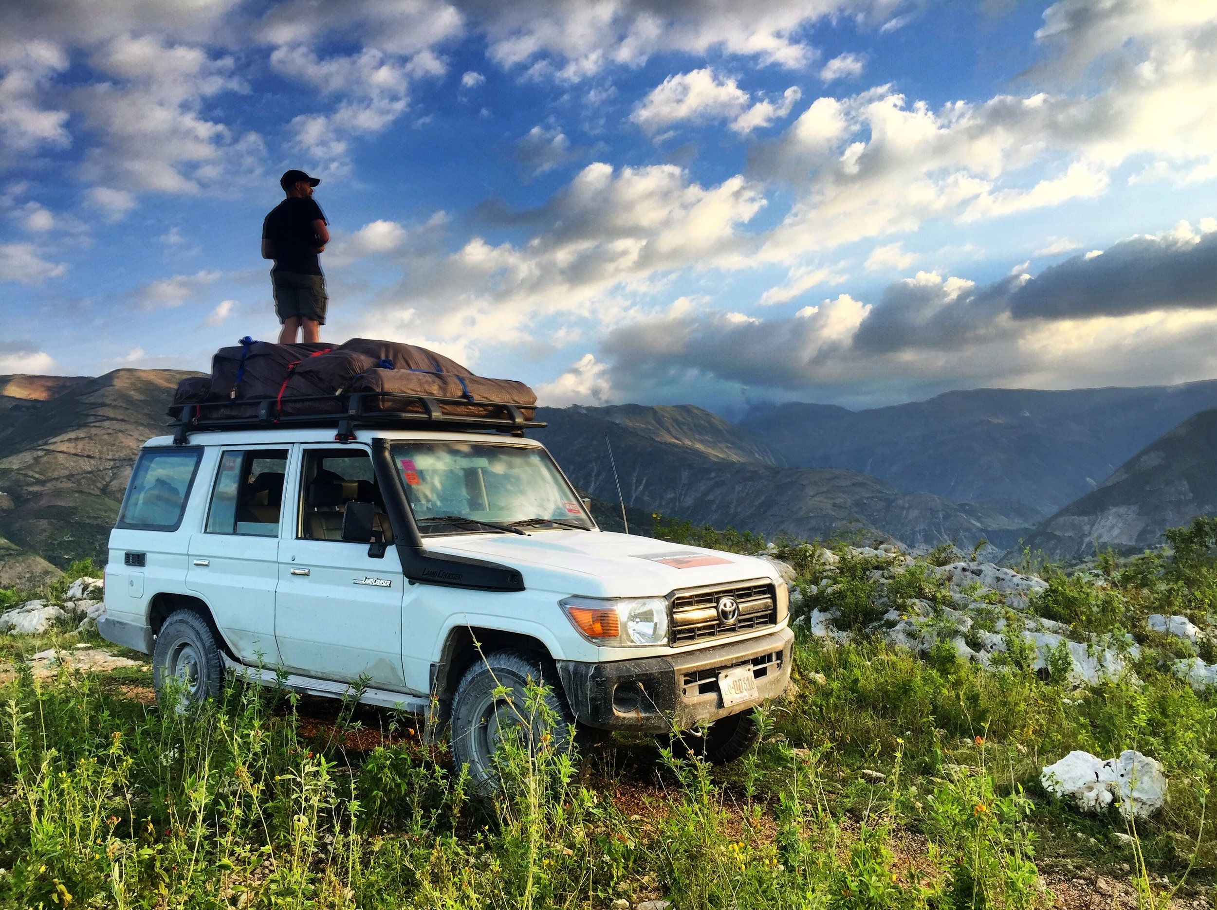 Director of Photography, Guido Ronge, standing on a Land Cruiser looking at the errosion damage to a river valley in Haiti