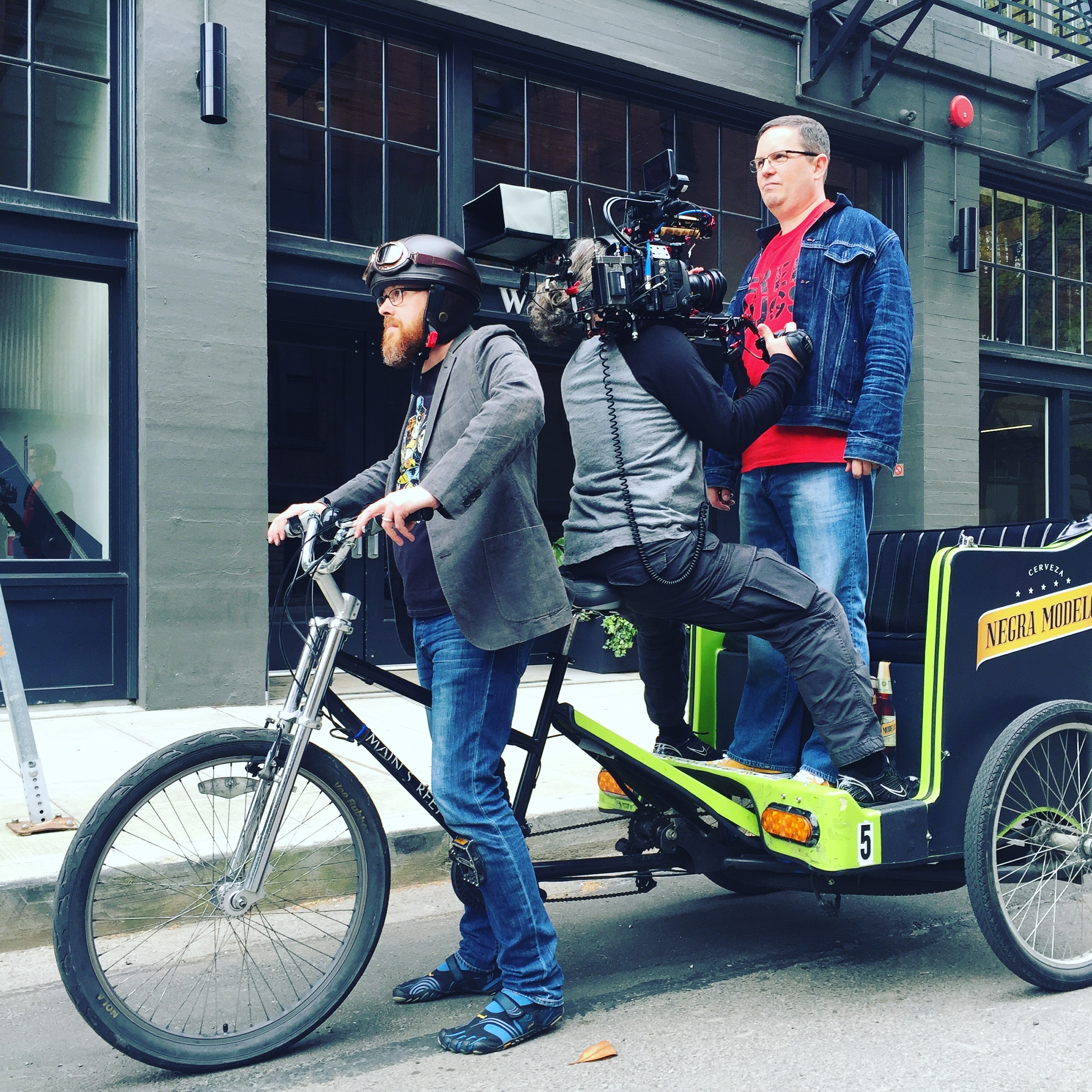 modern bike-pulled carriage with rider, driver, and director with video camera