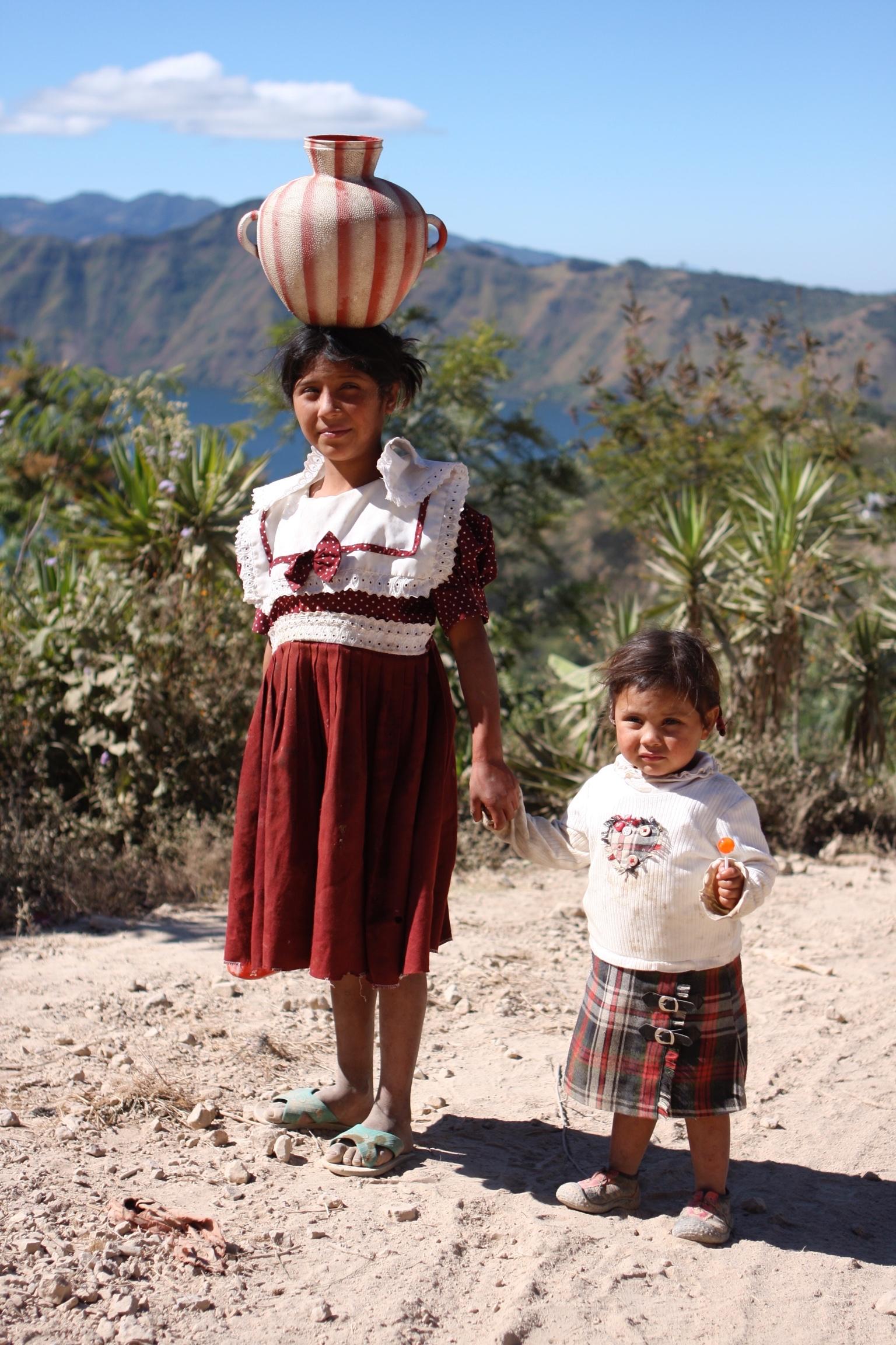 children in desert, older sister carrying pot on head, younger sister holding orange lollipop