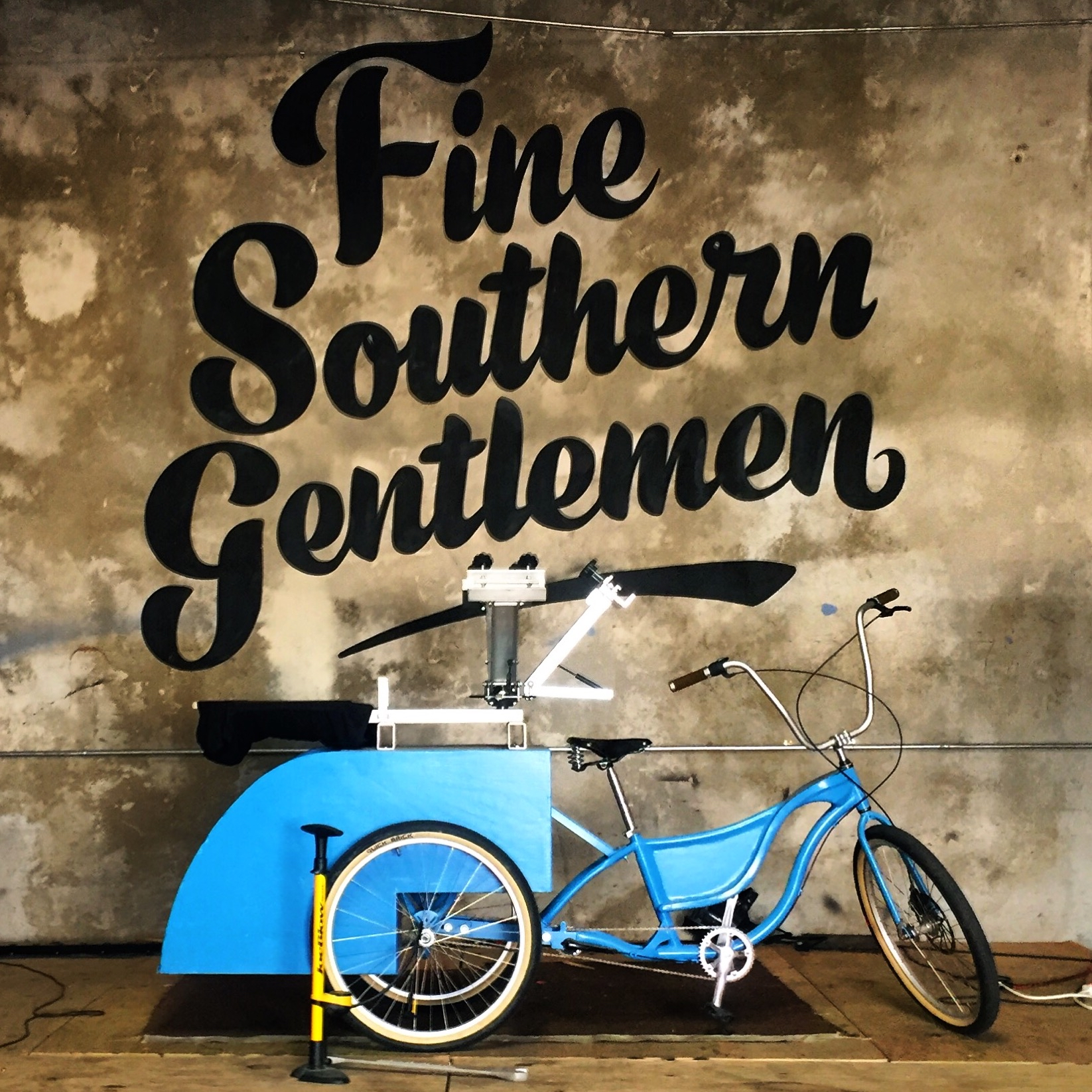 blue bike with contraption in back, fine southern gentlemen on wall