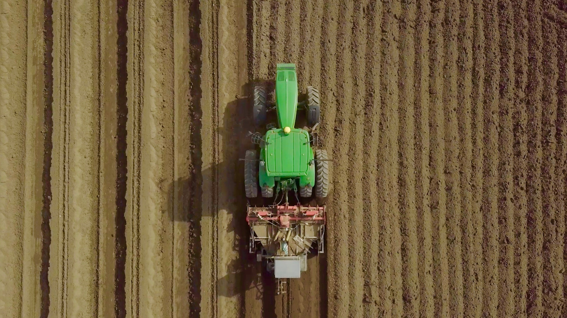 green tractor plowing field from above