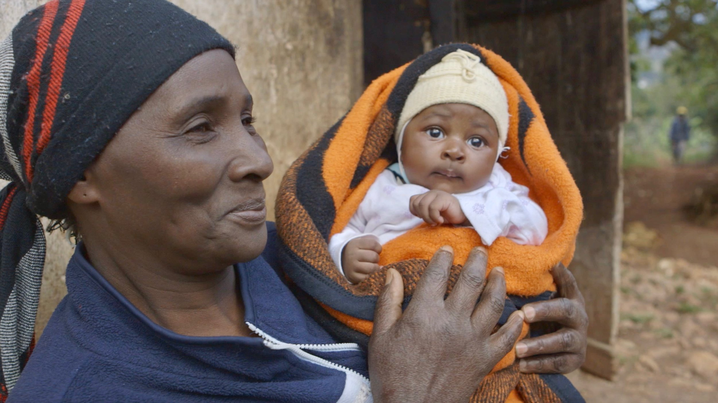 woman holding baby in traditional carrier