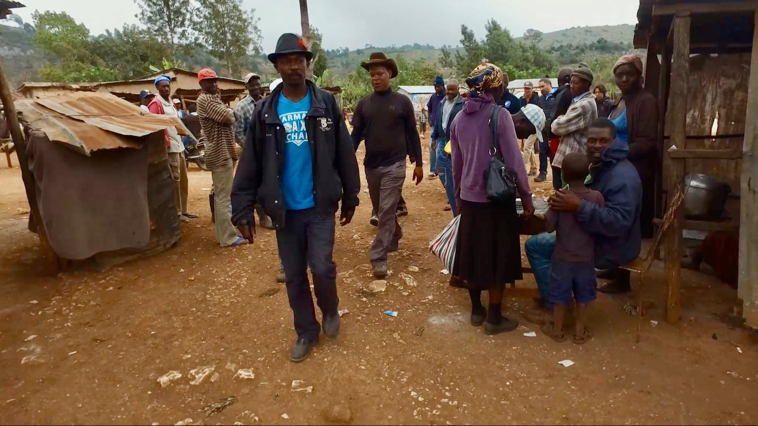 people walking on dirt road with permanent and makeshift structures