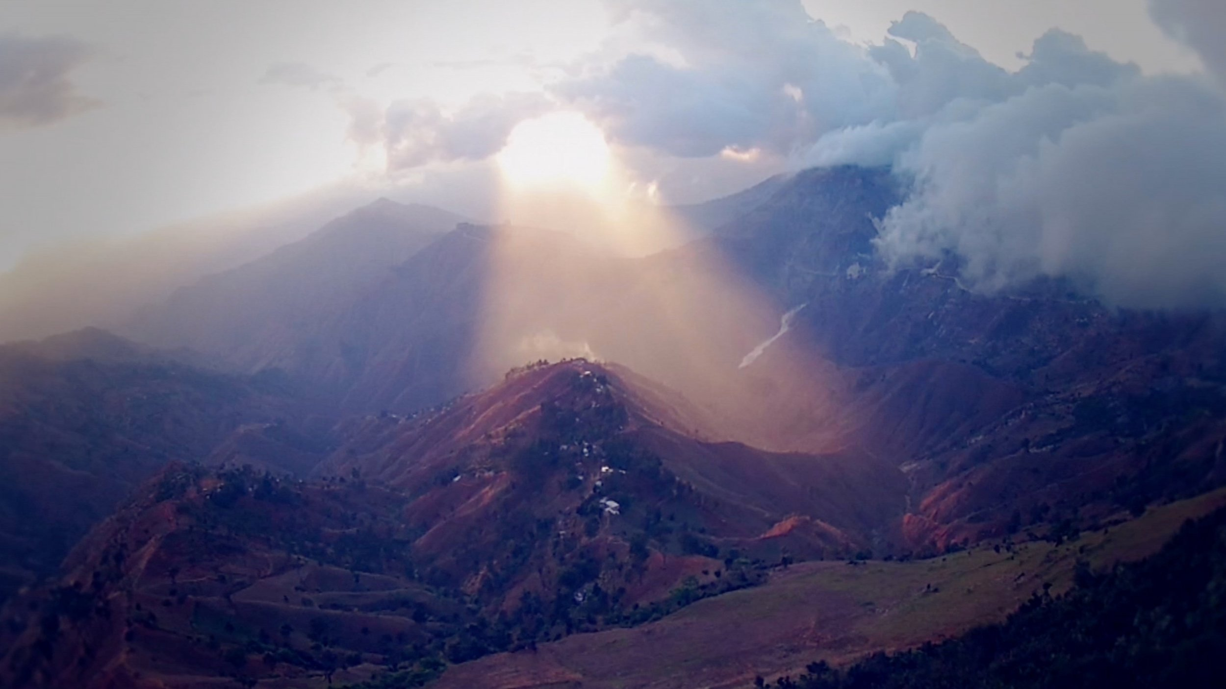 sun breaking through clouds onto hills like beam of light from Heaven