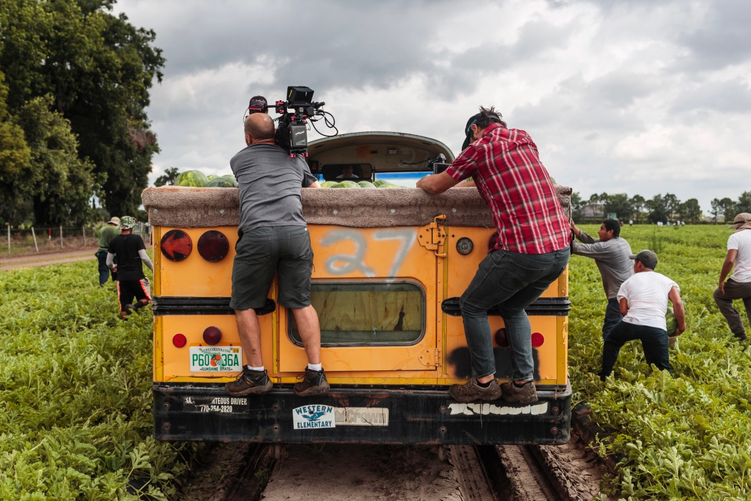 two men standing on back of truck in farm field filming with workers surrounding