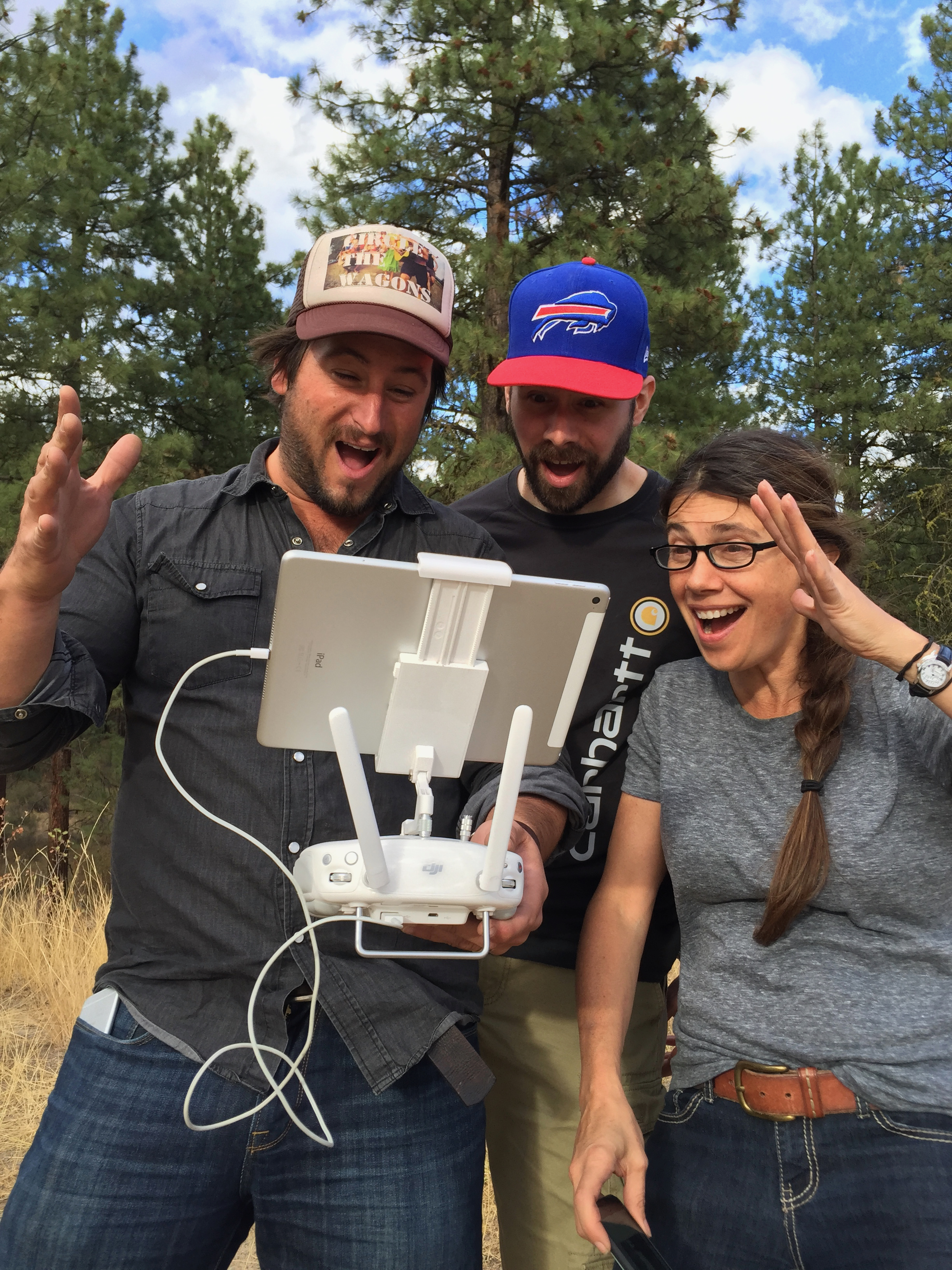 three people watching video for first time after recording in woods, excited
