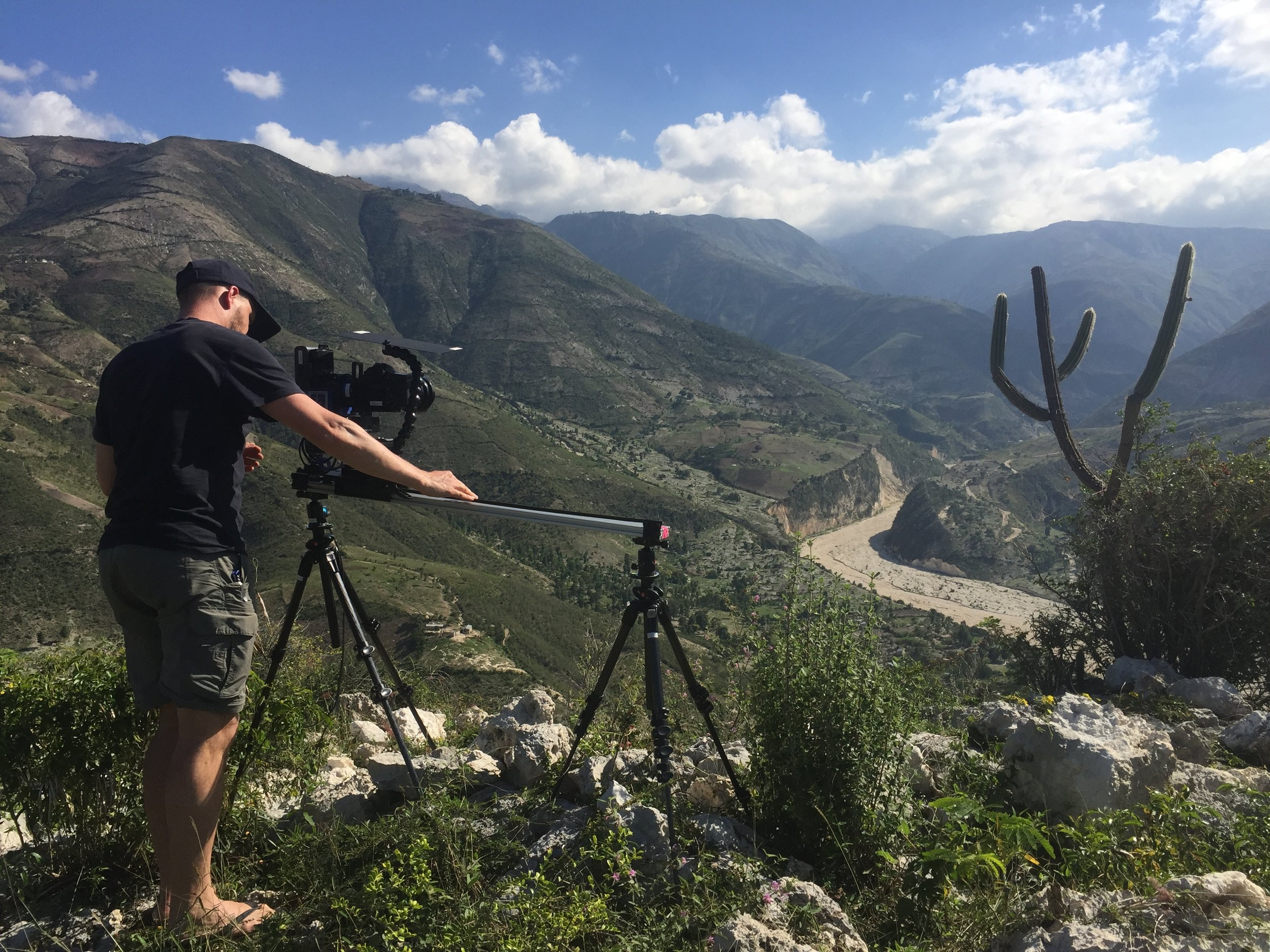 photographer using slider in nature, filming valley