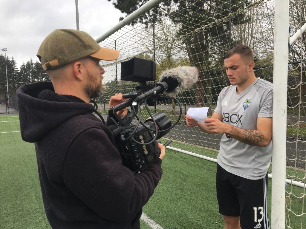 Jordan Morris reading script by soccer goal with camera man