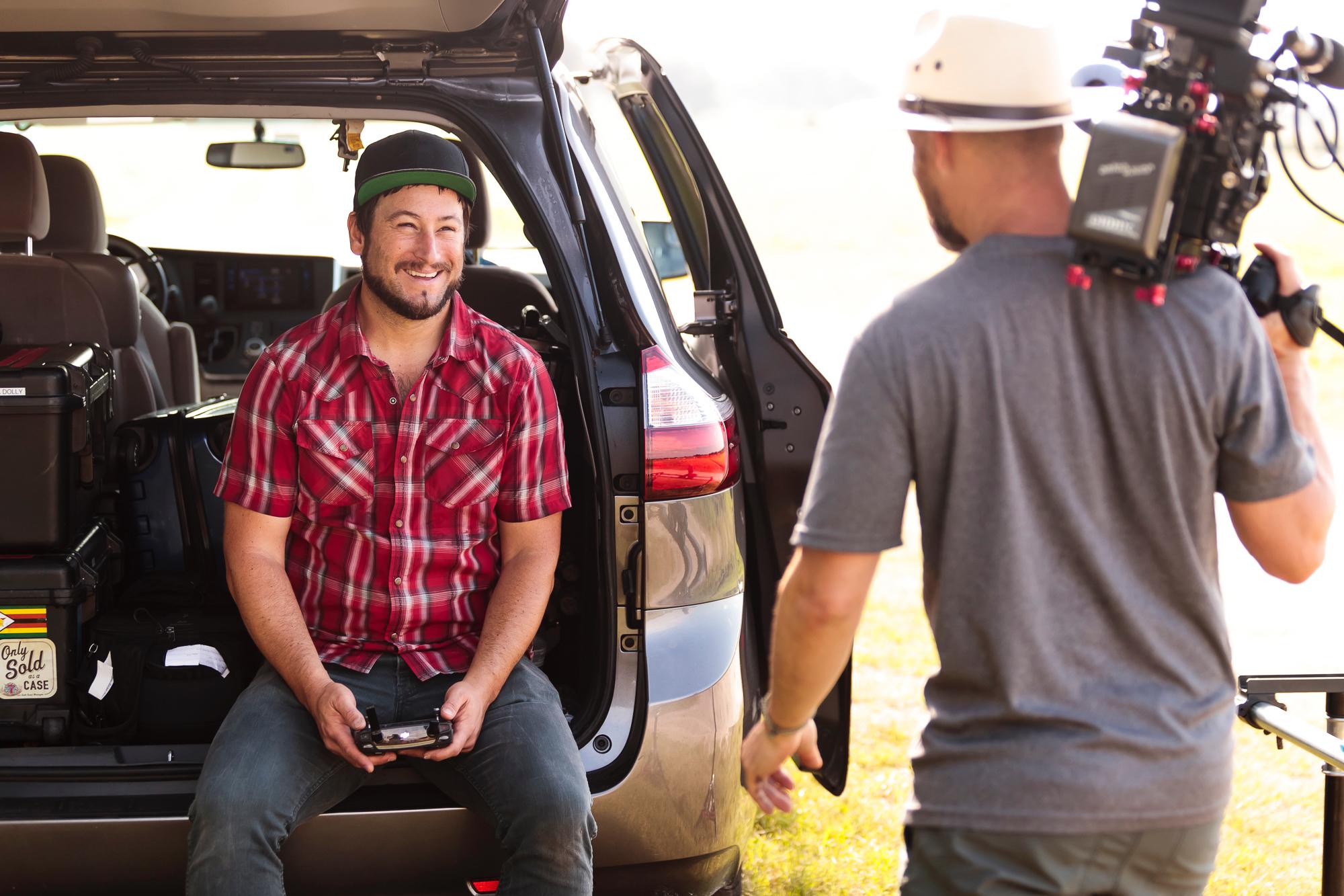man filming other man sitting in van hatch