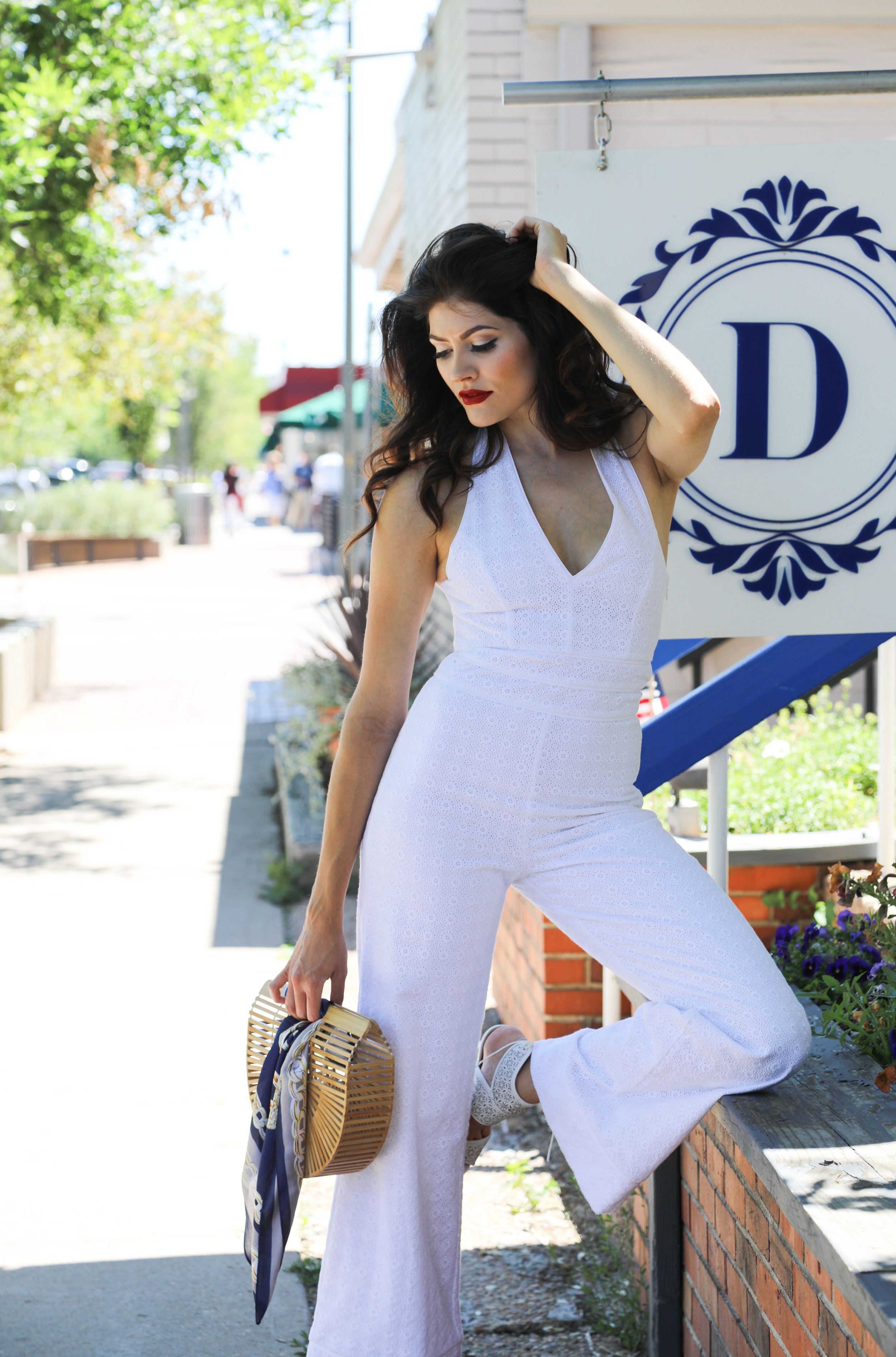 Hailey at Denver Darling Boutique on 3rd Avenue between Columbine and Josephine Streets wearing a white Lauren James Bridgette Jumpsuit.