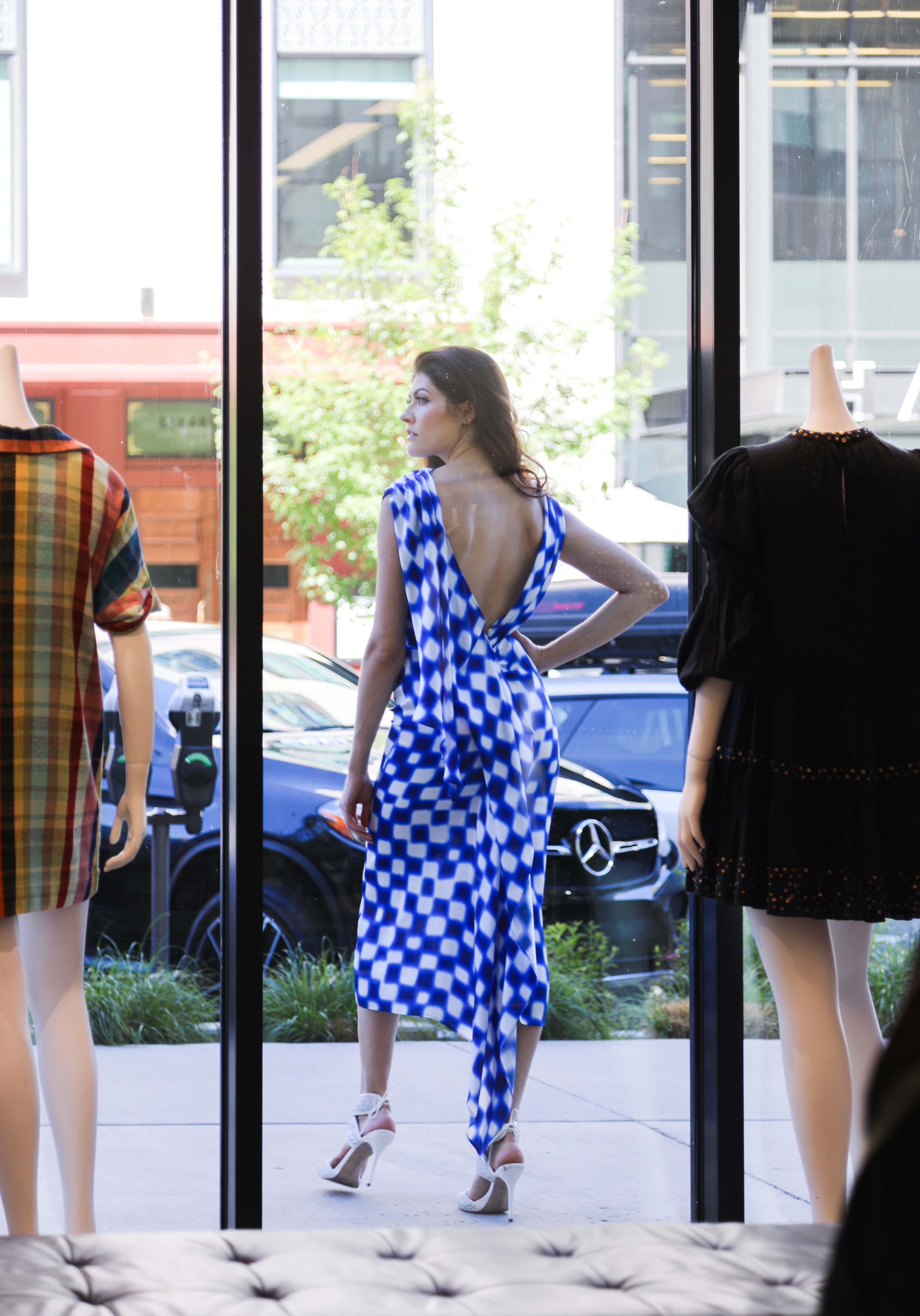 The view from inside Max Clothing Store of Hailey on Columbine Street wearing a Dries Van Noten dress.