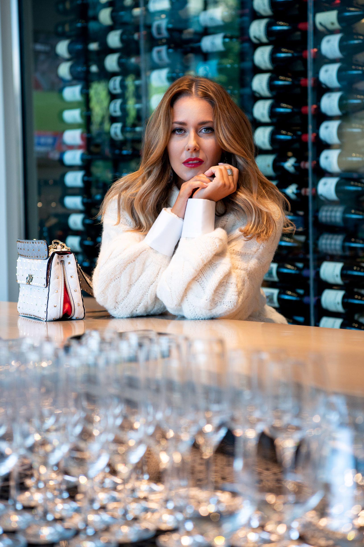 Sweater: Brunello Cucinelli, Pants: Ralph Lauren Collection, Wedge heel: Christian Louboutin, Earrings: Alexis Bittar, Ring: Freida Rothman, Bag: Valentino