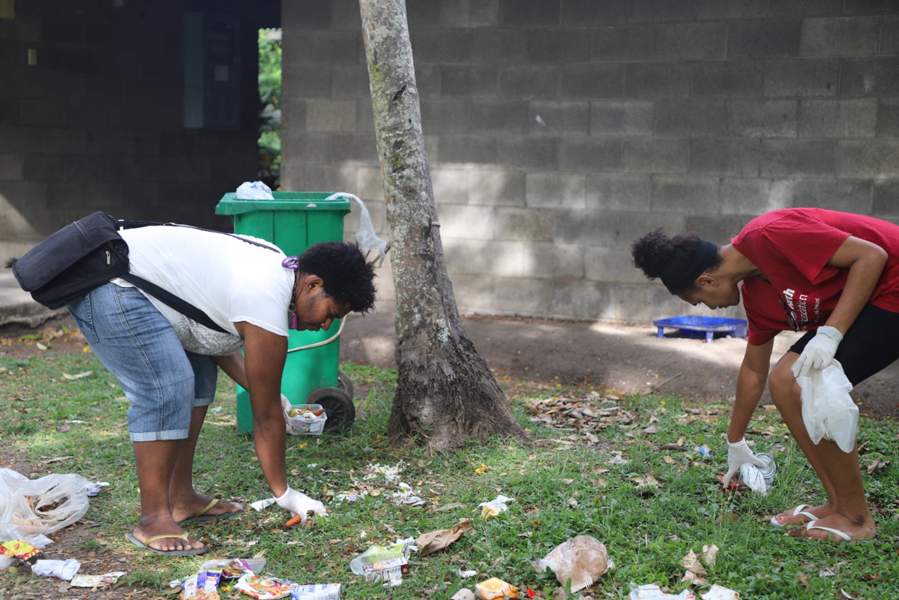 OSF Scholarship recipient Joy Martin (left) and a UPNG SMHS student collecting rubbish that were pulled out of the rubbish bin by stray dogs and placing them back into the bin. Once the new wheelie bins are placed in dormitories, the dogs will not be able to easily access the bins inside the dormitory halls.