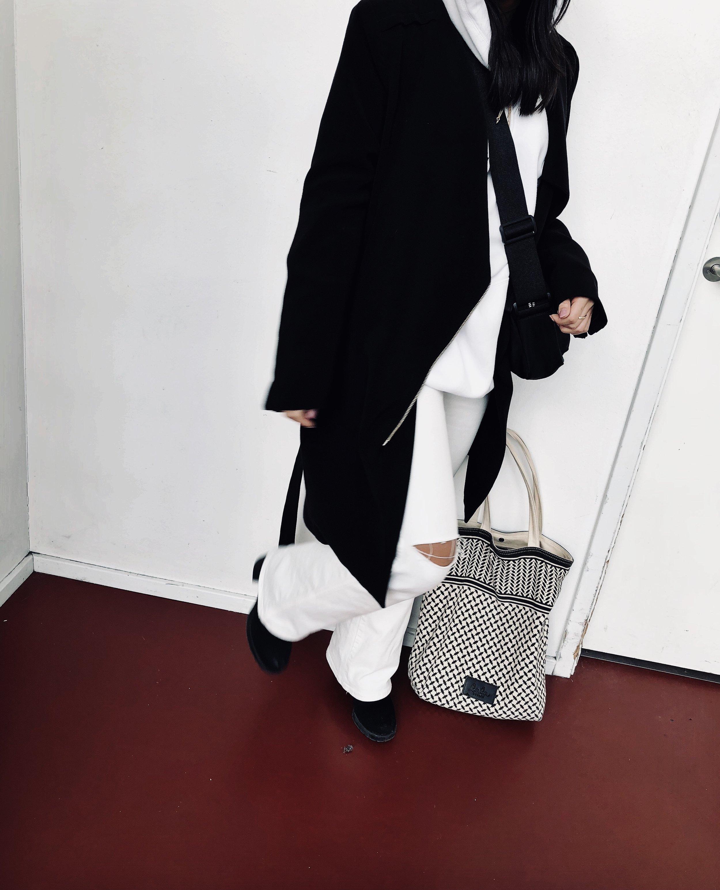 Amanda er iført hættetrøje fra Weekday, bukser fra Zara, støvletter fra Vagabond, En sort frakke, skuldertaske fra Astrid Olsen x Na-kd og en tote bag fra Lala Berlin.