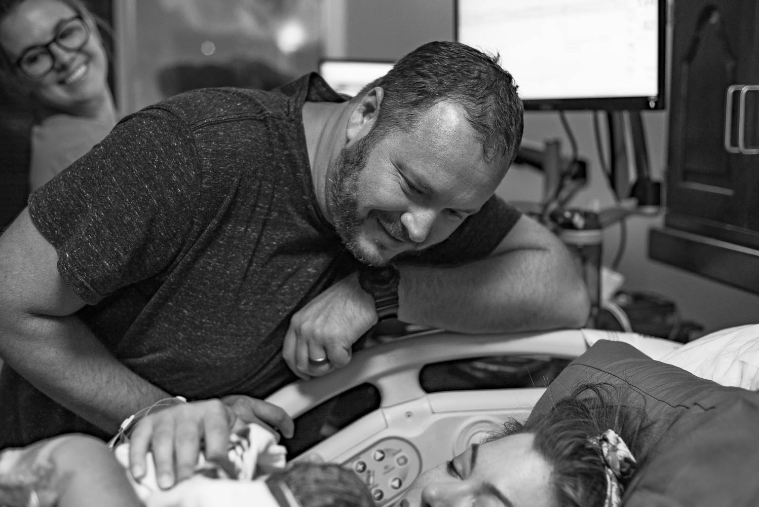 Dad smiling down lovingly at his new daughter while she lays on Mom's chest in the hospital bed.