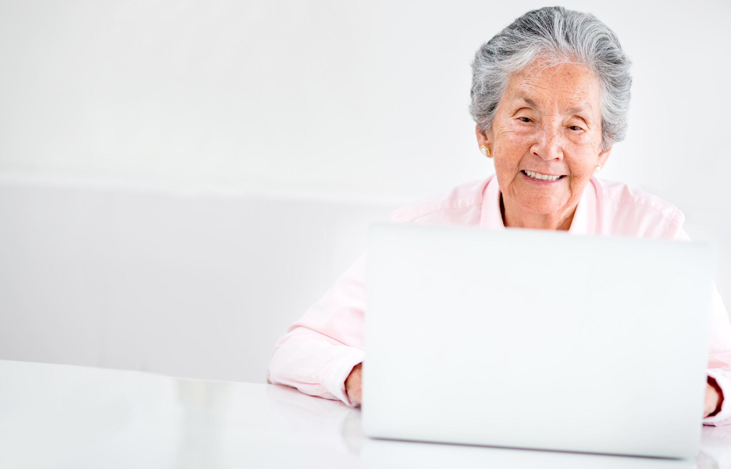 Retirees often lose access to their enterprise account, but still need access to services. Cirrus solutions allow organizations to link retiree accounts to an externally hosted credential. In this photo, a retired woman logs in using a computer.