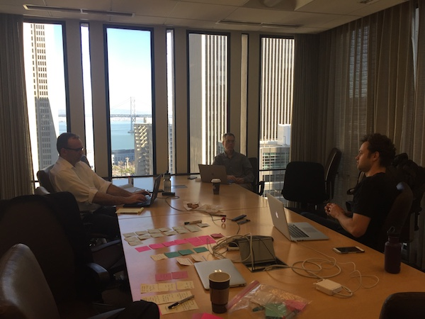 Photo of team collaboration around a board room table.