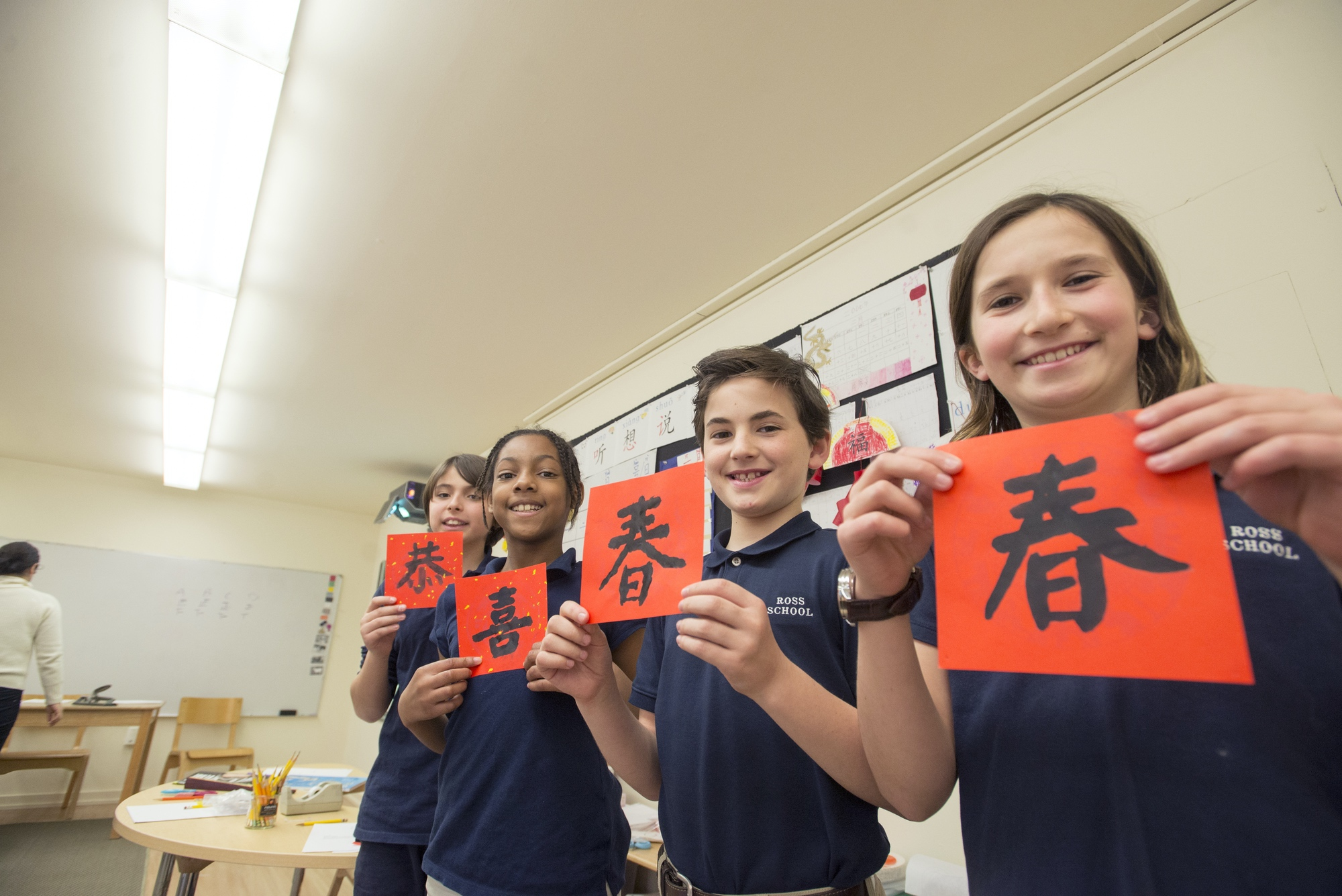 Ross Elementary School students hold up Mandarin language signs as part of their study of the language which begins in Kindergarten