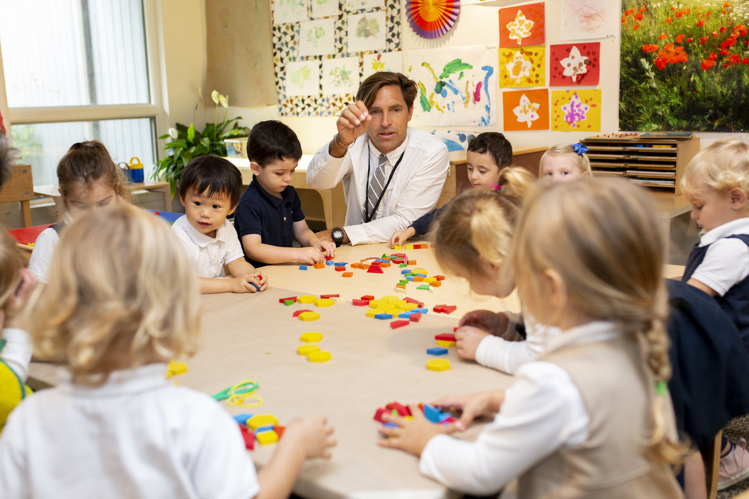 Ross Early Childhood teacher with nursery students engaged in hands-on learning using colorful wooden blocks.