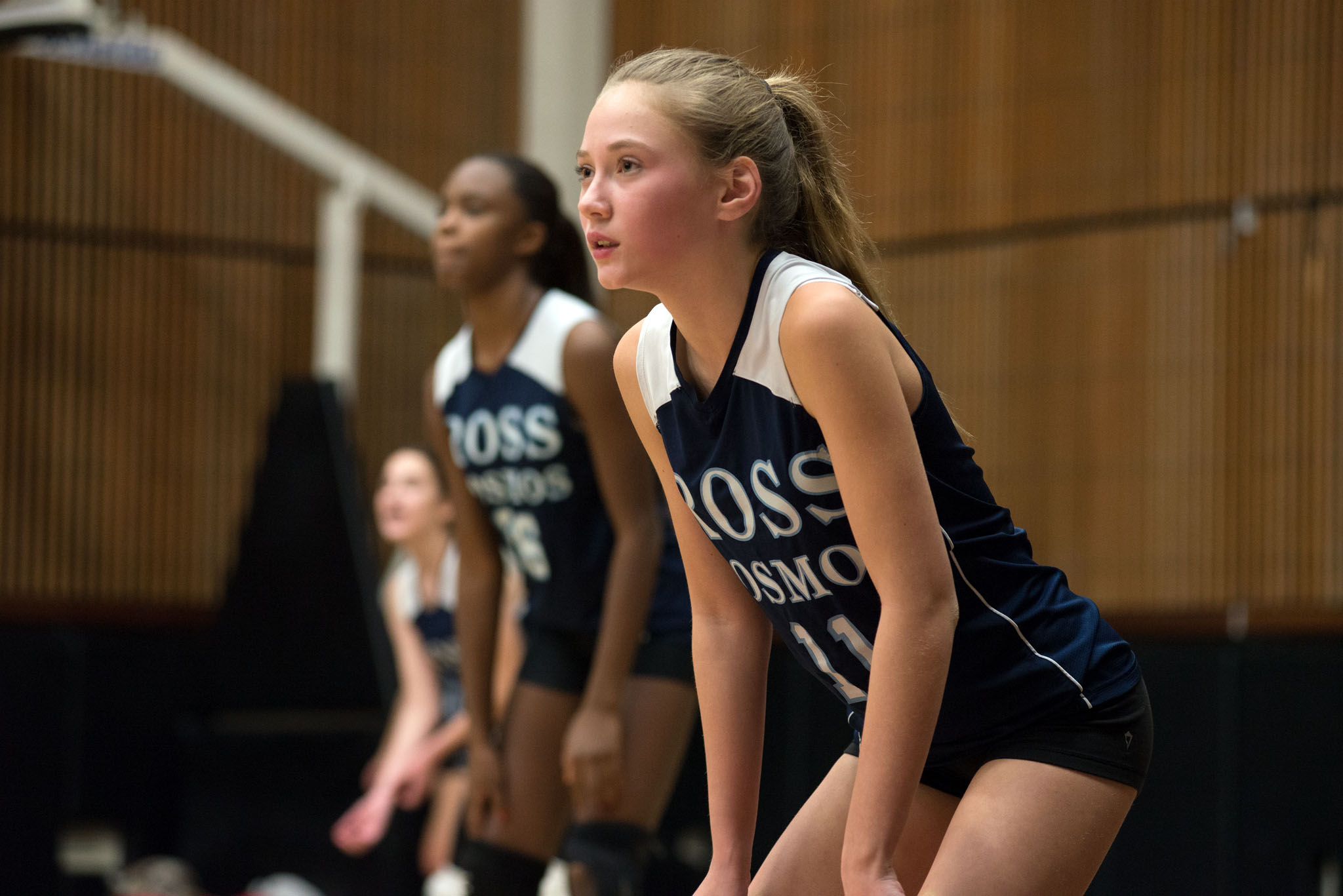 Ross High School Girl's Volleyball team in athletic uniforms, ready to begin play.
