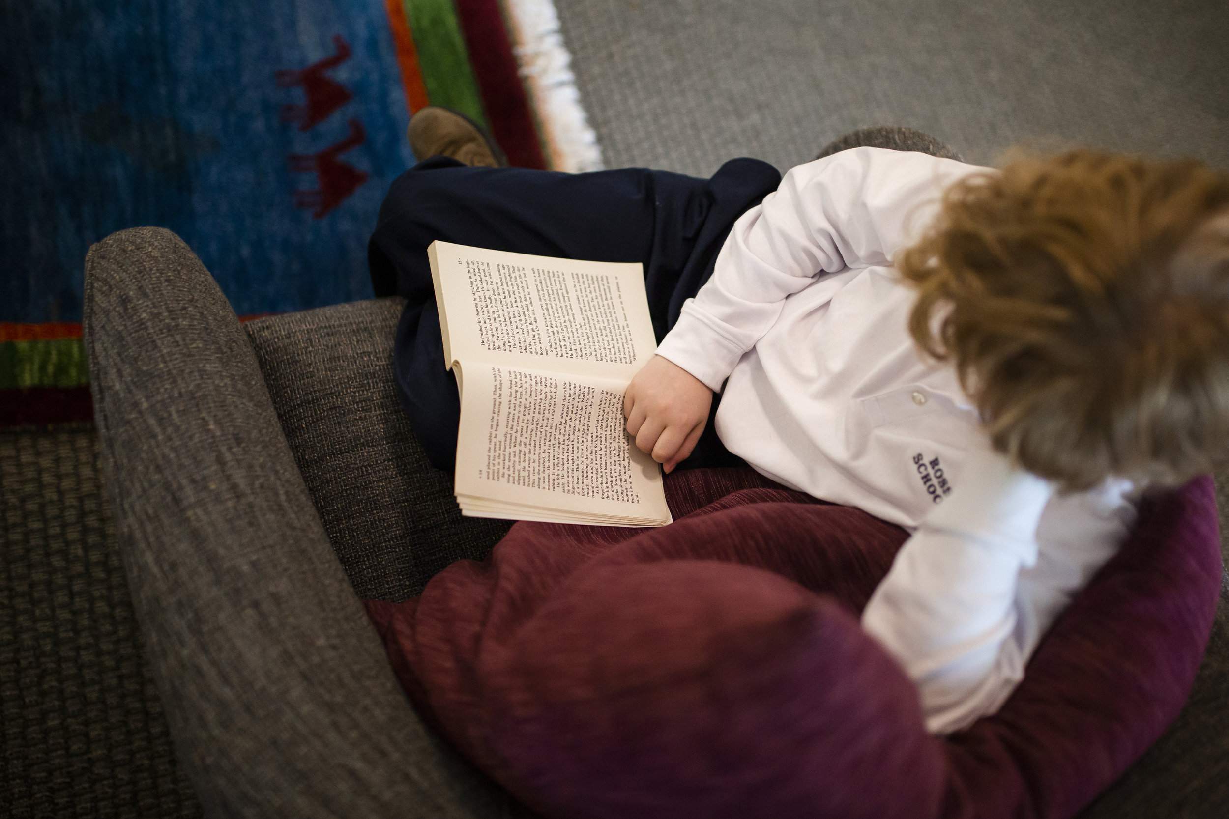 Ross Elementary student reading a book in a comfortable chair in one of the Ross School libraries.