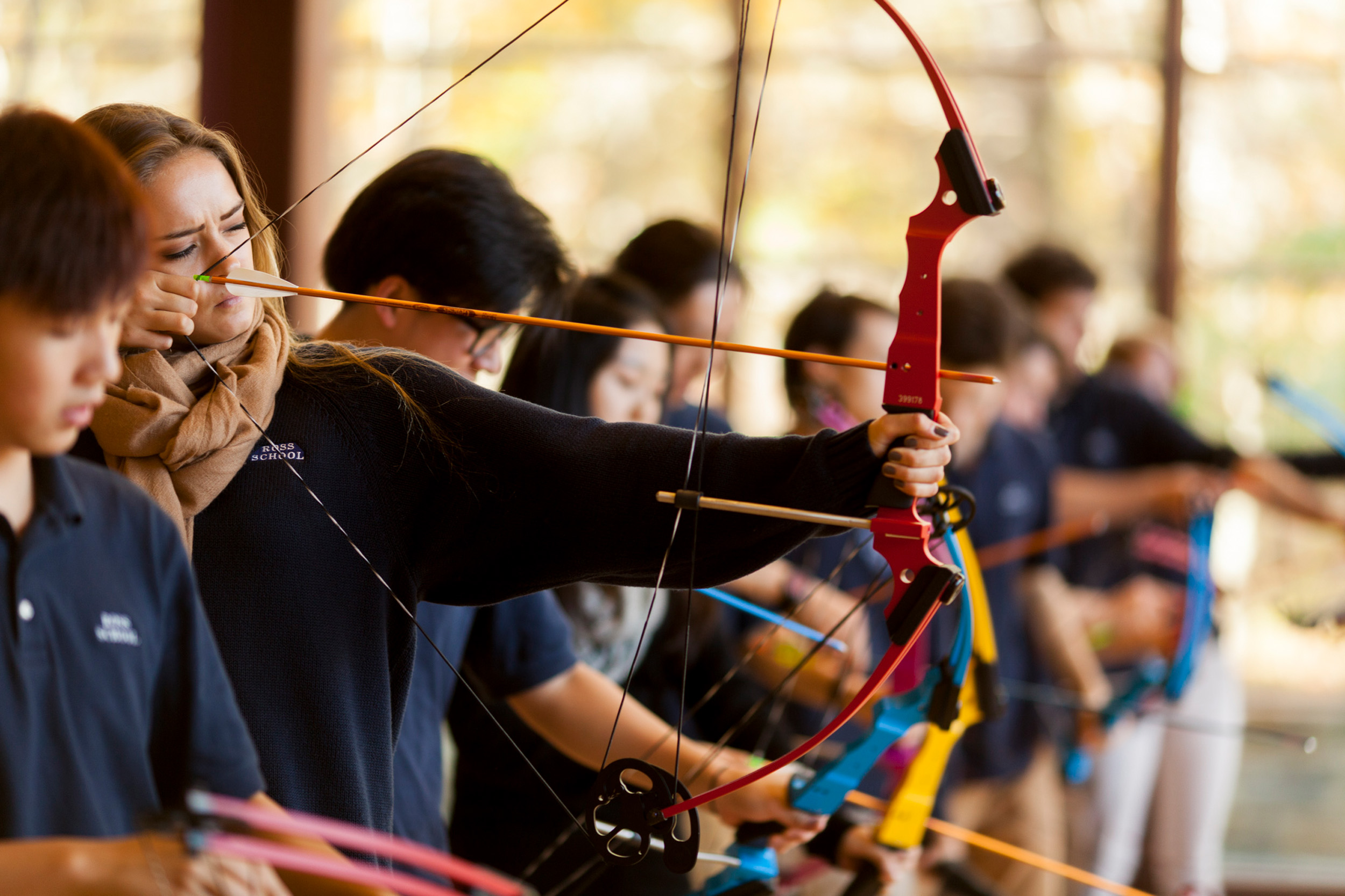 Ross Upper School students engaged in archery lesson.