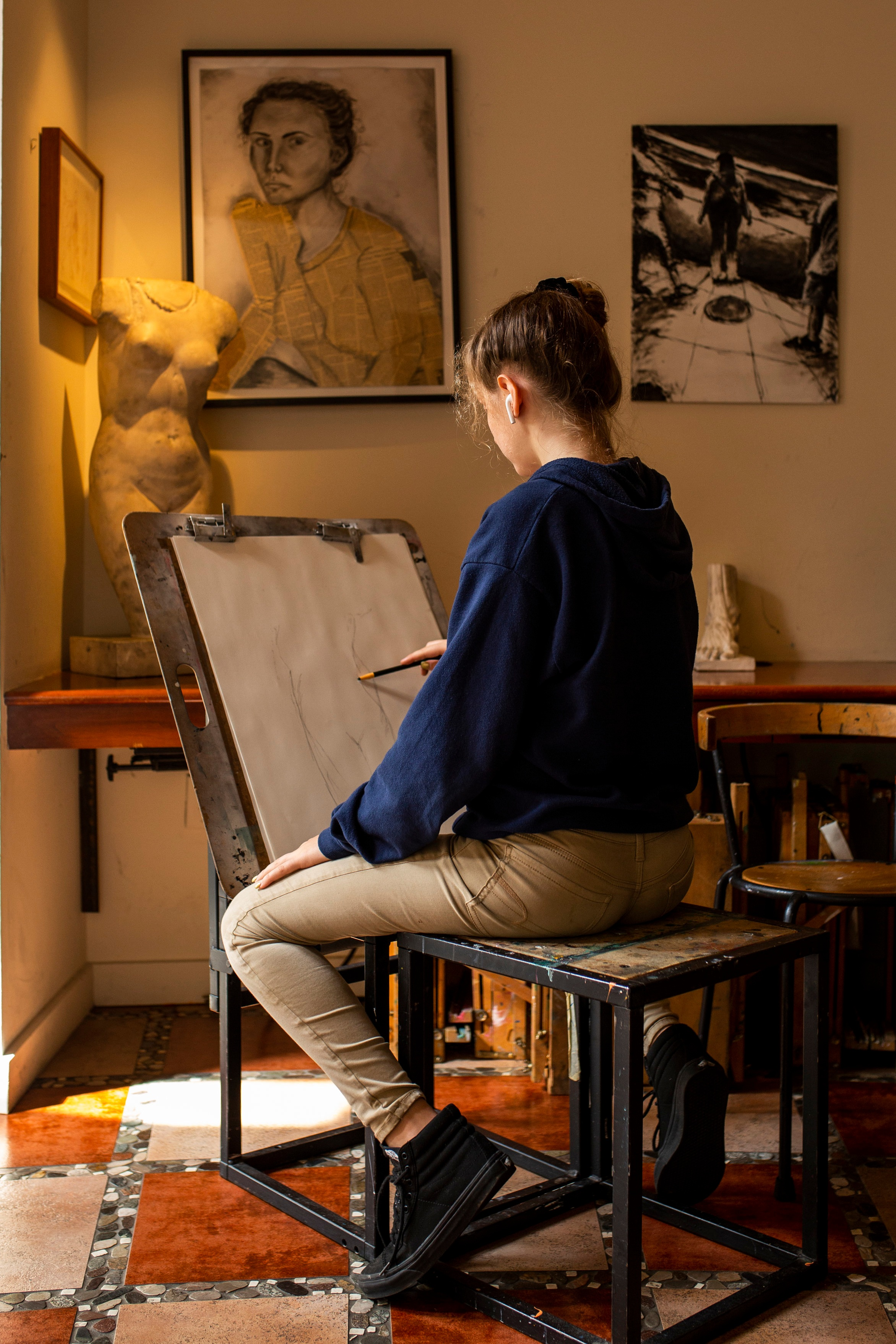 Ross Upper School student sketching at her easel, surrounded by replicas of iconic drawings and sculpture.