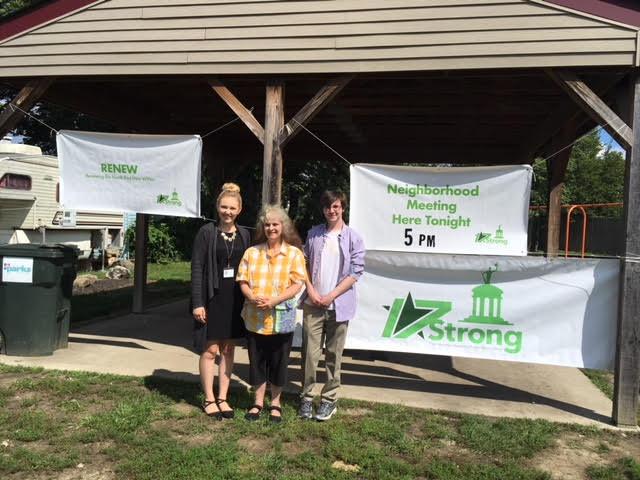 Community Member, Ruth Meadows, helps VISTAs hang banners for the neighborhood RENEW meeting.