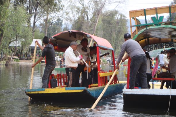Marichi on a boat sidling up to some tourists in Xochimilco. (photo: Brent Petersen)