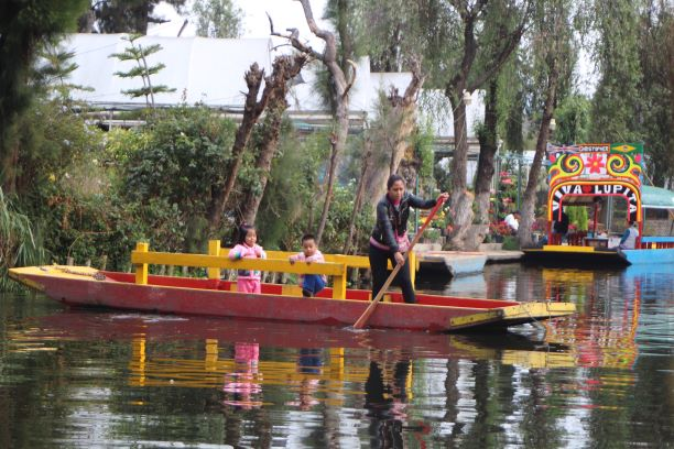 A young woman who lives in Xochimilco transports her children in a boat (photo: Brent Petersen)