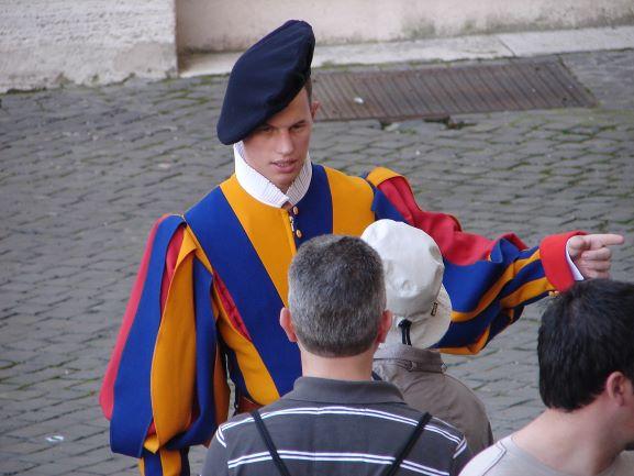A colorfully dressed Vatican Guard helps a tourist