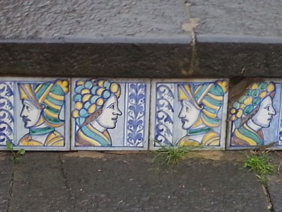A close up picture of some of the tiles on the staircase. Notice the damage on some of these very old tiles.