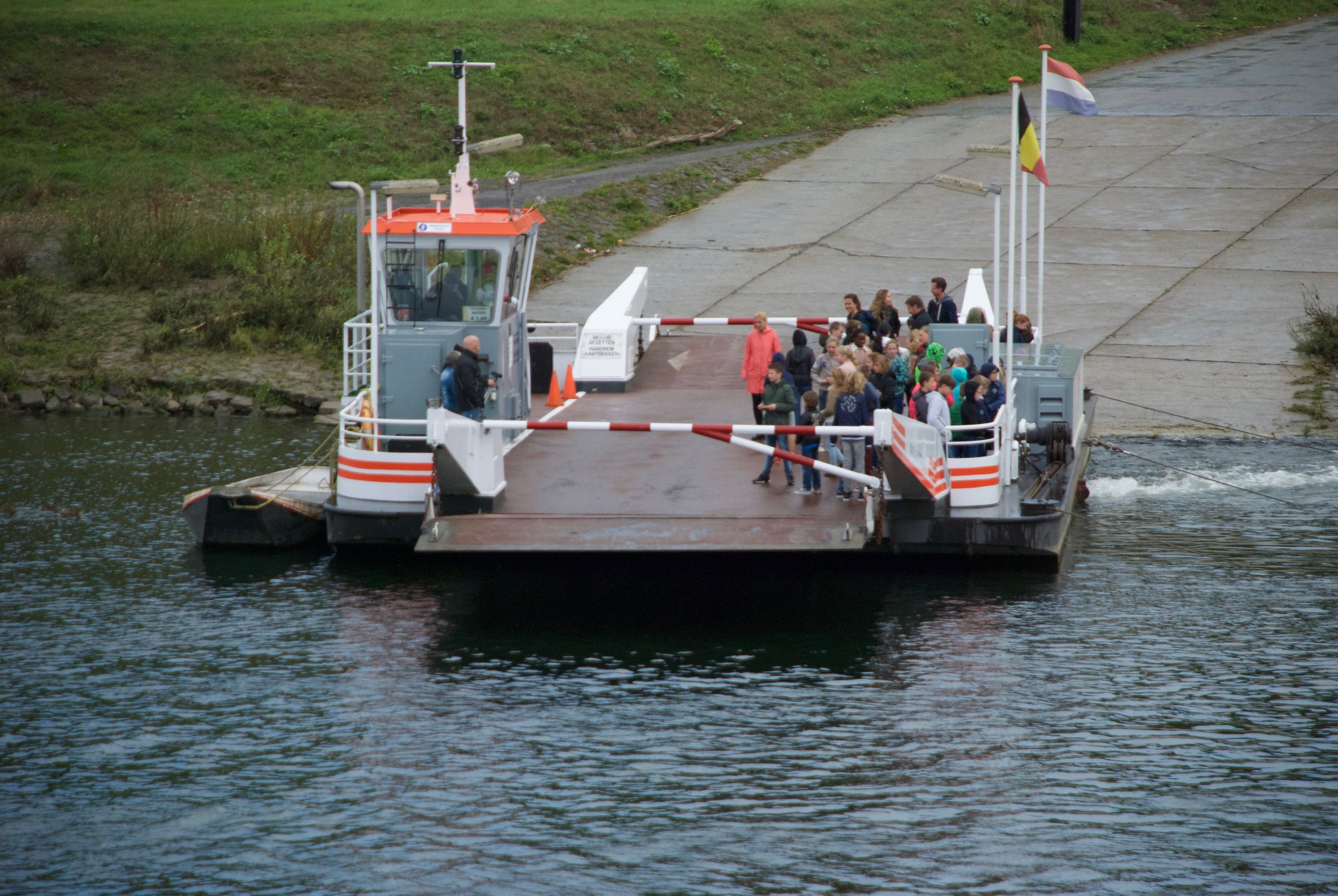 kinderen uit Nederland steken met pont de Maas over