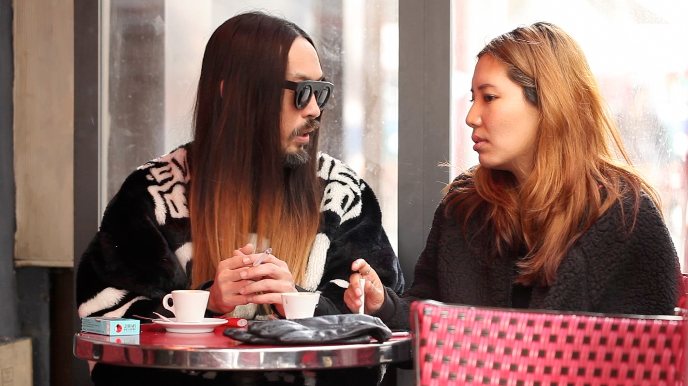 Royal Cafe Tenzin Dazel, Rémy Caritey   2016   France   Drama   39'   Tibetan, English, German with english. Subtitles Screenplay: Tenzin Dazel Actors: Pema Shitsetsang, Tashi Gyalpo, Kyilay Namdol, and others.    Trailer    Tibetan gangsters? Violence, adultery or even homosexuality? Unimaginable themes for a Tibetan film. Or not completely? In her film, Tibetan director Dazel wants to honestly reflect the lived reality of Tibetans in exile - with all its corners and edges. She takes her inspiration from Café Royal in Paris, where Tibetans seeking asylum meet in the evening to exchange ideas and get rid of their everyday worries. As she collects ideas for her film, her own life happens, which is as turbulent as that of her protagonists. Language barriers, financial problems and doubts arise from all sides - the realization of her film seems almost impossible. But when Dazel can no longer refuse her own life, she finally realizes her dream. Thus a wonderful self-reflexive loop succeeds - meta cinema at its finest!