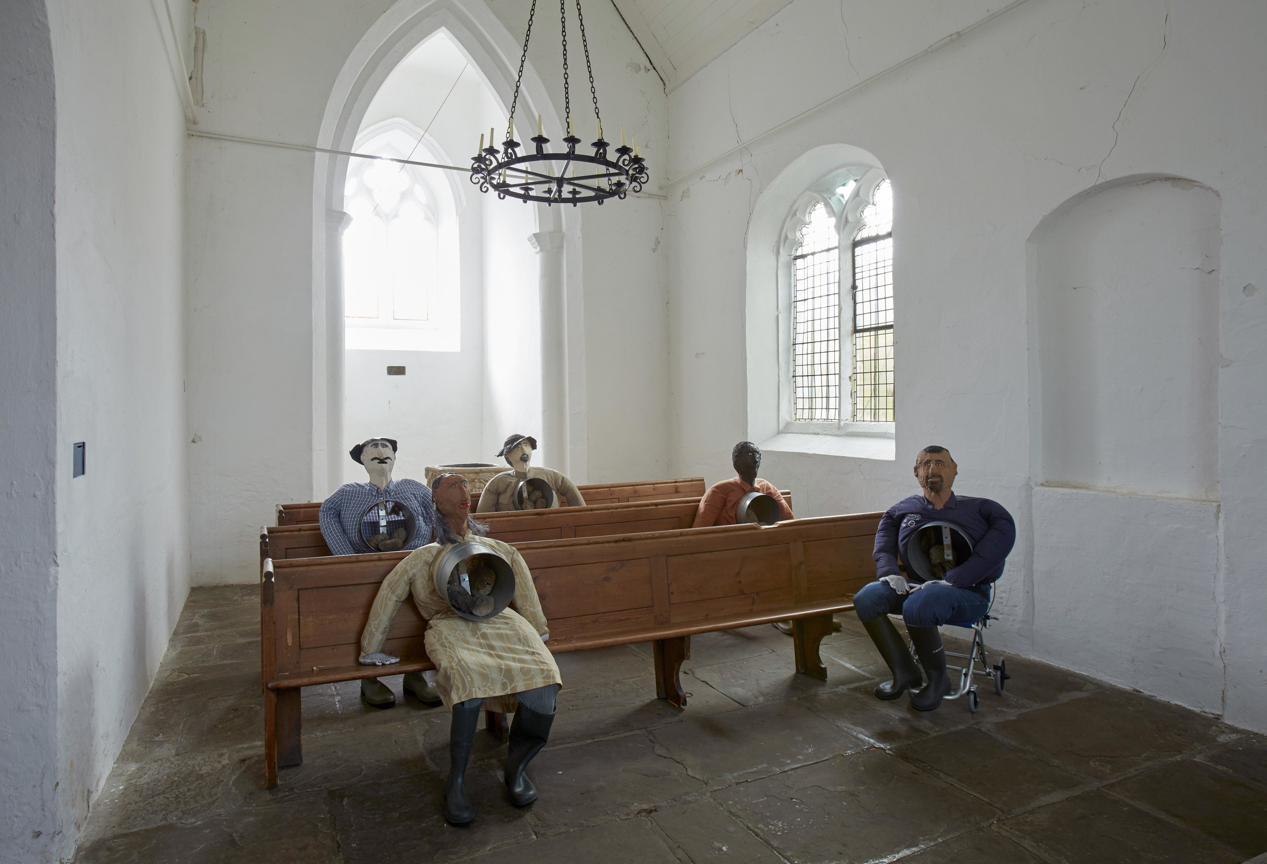 The Institute of Reconciliation, 2014–ongoing 5 papier-mâché and fabric effigies, church pews, burnt corn and clay - displayed in St Peter's Church (pictured before they were modified with a chainsaw)