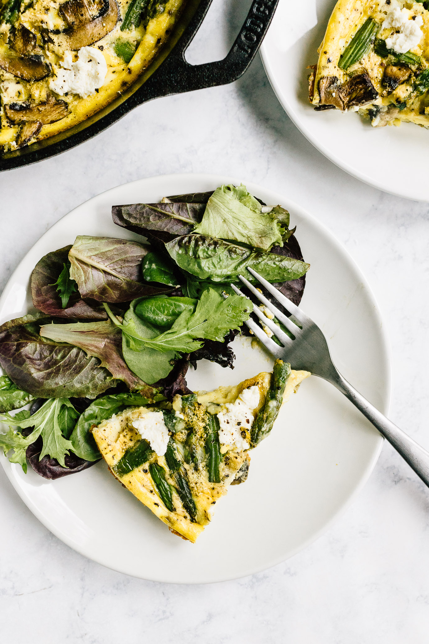 Slice of asparagus mushroom frittata with green side salad
