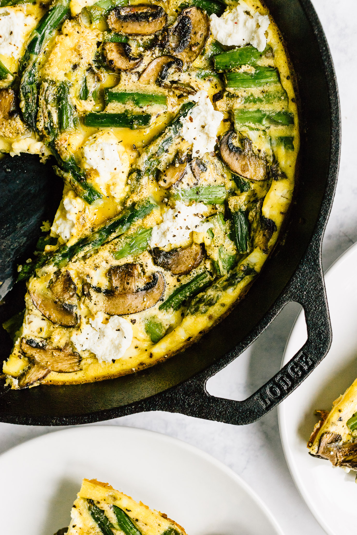 Slice of asparagus mushroom frittata and cast iron skillet