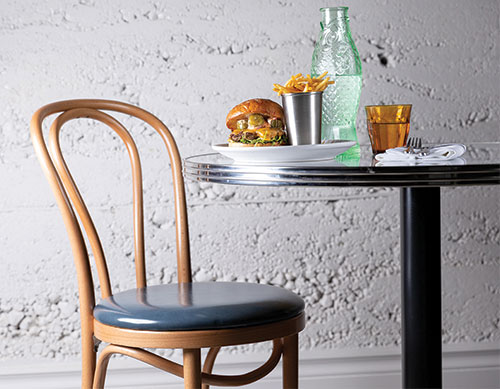 table and chair against white cement wall. On table is burger, fries, glass of water, green fish-shaped carafe filed with water.