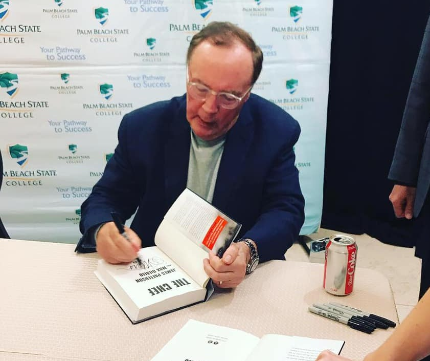 James Patterson signing a copy of his latest novel, The Chef!