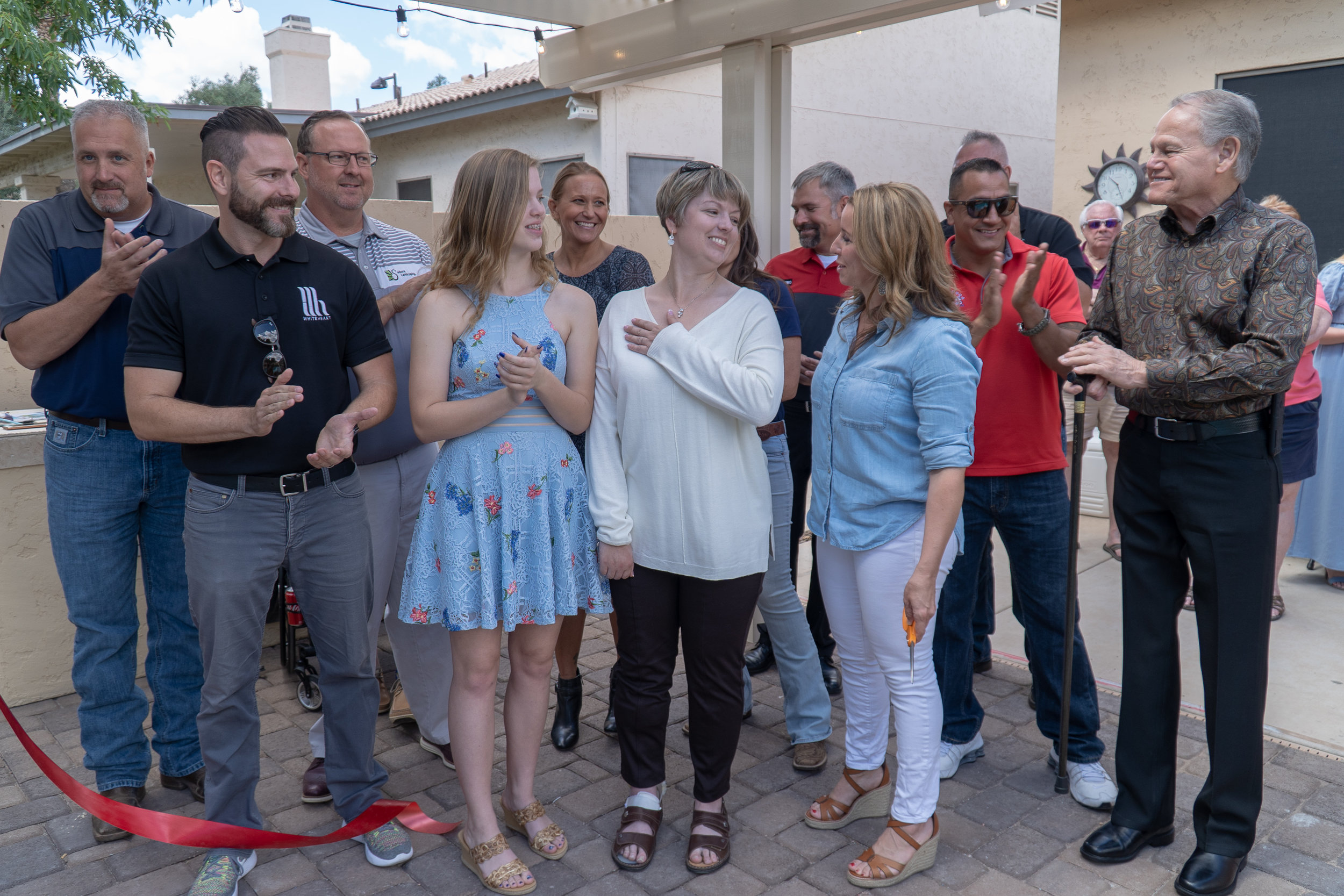 HMC Katke (center) smiles at the ribbon cutting for her new therapy pool.