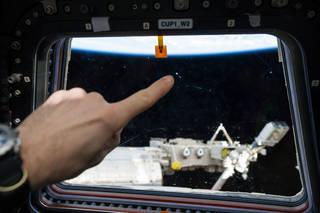 Scratch on ISS window from micro meteor orbital debris. Credit: NASA