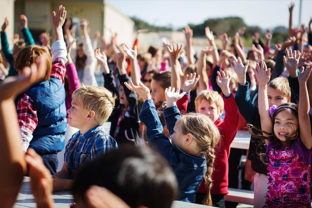 Students lifting their hands during chapel
