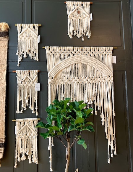 Macrame wall hangings hang behind a tree in the front of Someday.