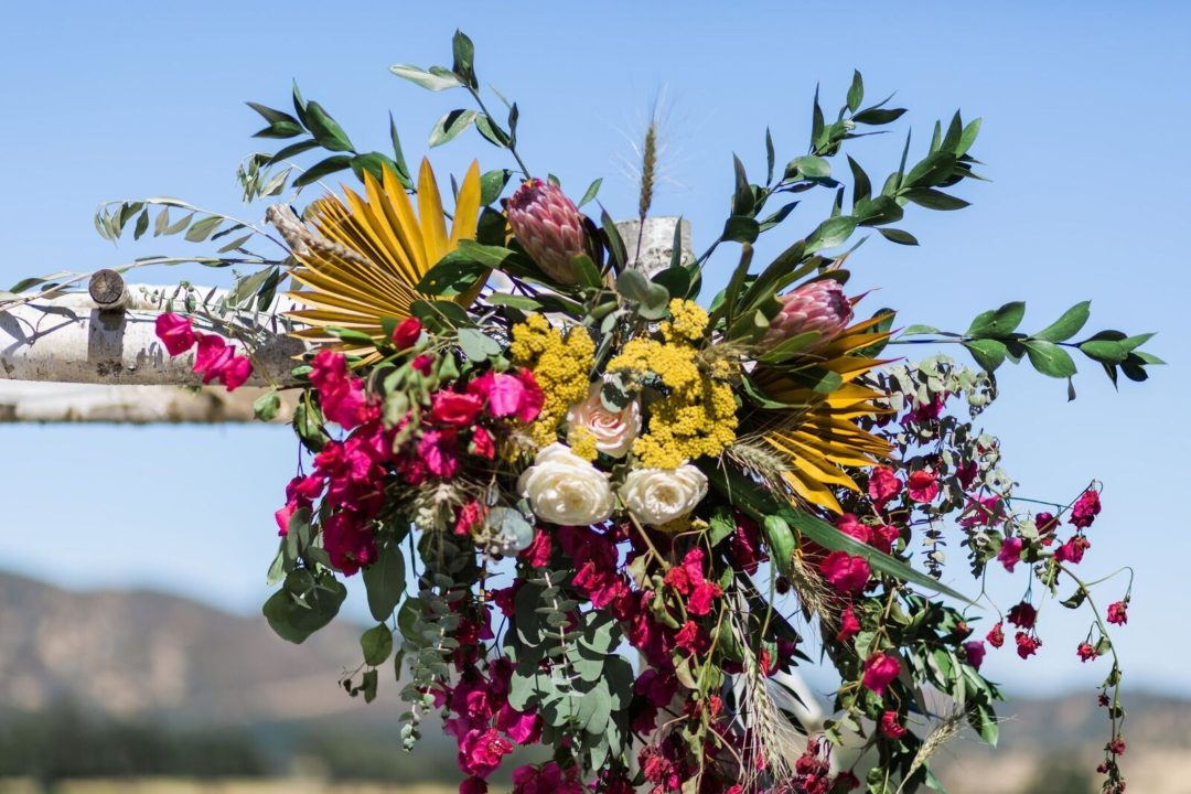 12-Central-Coast-House-of-Design-–-Yvonne-Baughman-–-Paso-Robles-LGBTQ-wedding-Central-Coast-LGBTQ-wedding-planner-Oyster-Ridge-Barn-Wedding-natural-wood-chuppah-with-wildflowers-1080x720.jpg
