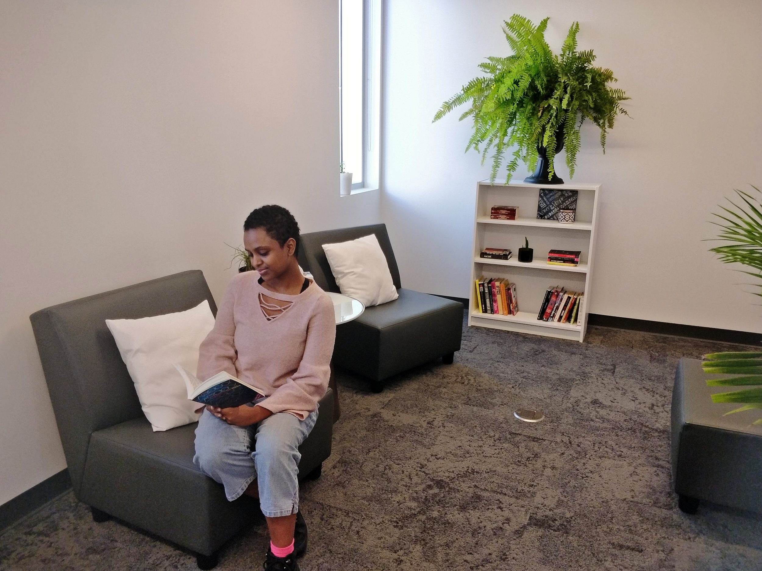 Pictured here, student student staff taking a look at the library in the YFS Wellness Centre. Get comfortable with a good book from 10AM to 4PM, Monday to Friday.