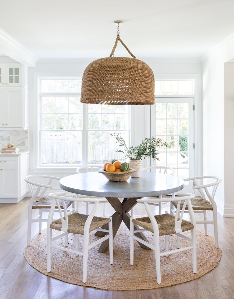Love the statement woven pendant light, wishbone chairs and round jute rug in this beautiful breakfast nook from Salt Design Co #dining #homedecor #diningroom #kitchennook #breakfastnook #diningnook #nook