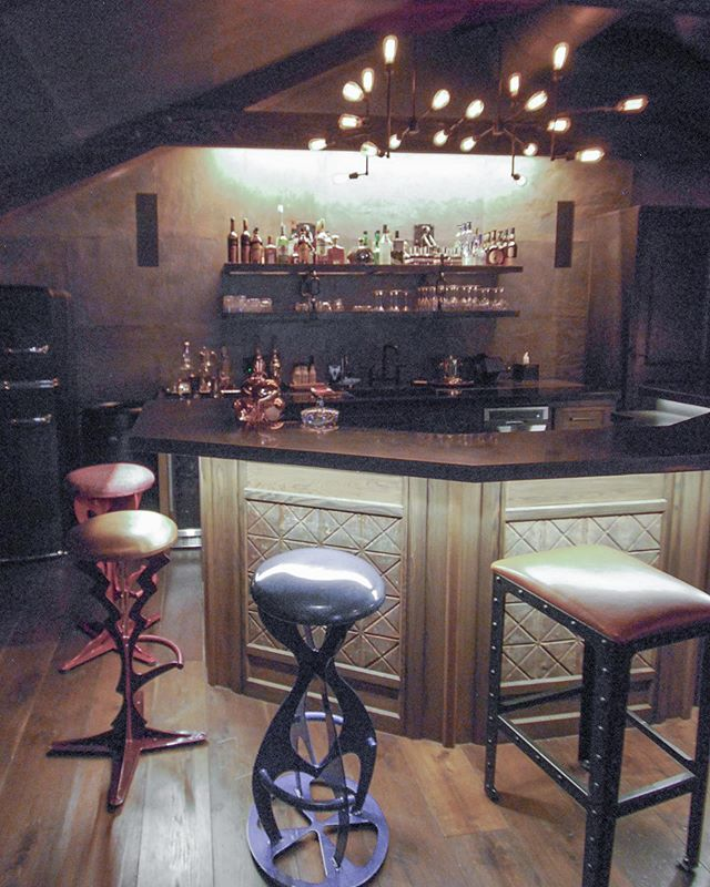 """Cheers to Friday 🥃 Are you going out or staying in this weekend? I'd be happy to stay in at this home bar/man cave we finished a few years ago. 👉swipe to see behind the bar, the original concept sketch, and the before photo! * We added everything you see here including the huge beams. Lots of fun custom details in this space. The metal panels in the bar front and cabinet doors are rusty reclaimed ceiling tiles I found at the Alameda Flea Market. The bar shelves were custom made by @chmetaldesign including serious chain links and brackets. Our client had these wacky bar stools that add some fun color to the room. Custom concrete countertops. Reclaimed barn wood walls. The wall behind the bar is a real stone veneer wallcovering by @phillipjeffriesltd - to truly make it a """"cave"""" 😆"""