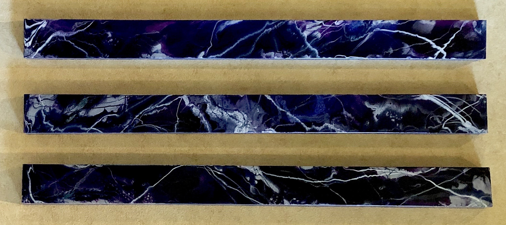 Title unknown, 2018. Acrylic, pigment and resin, 5 x 60 inches, set of three.