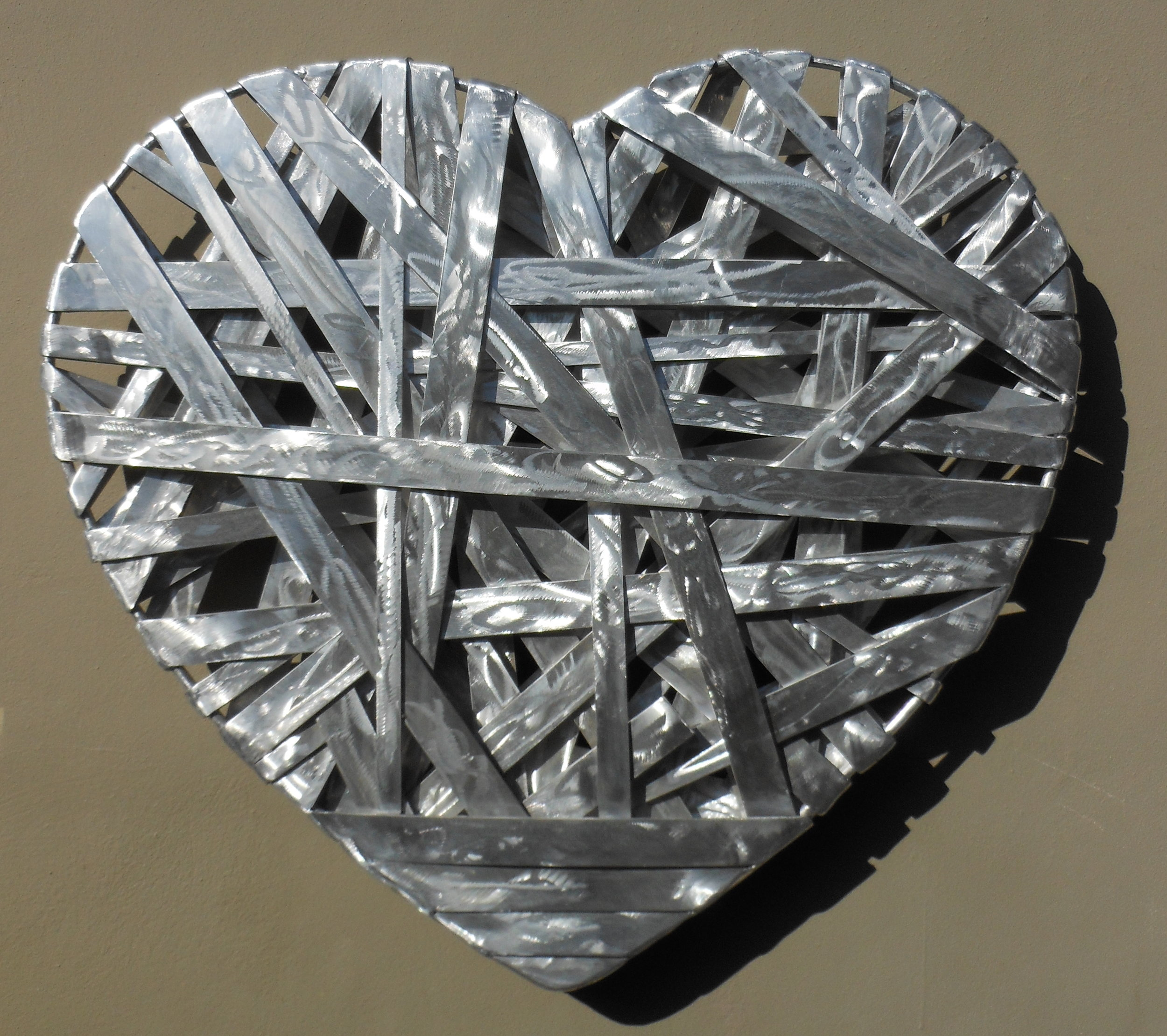 Cariad is Welch for Love. Aluminum welded flat bars and round solid stock on the outside, 36 w x 36 h x 6 d.