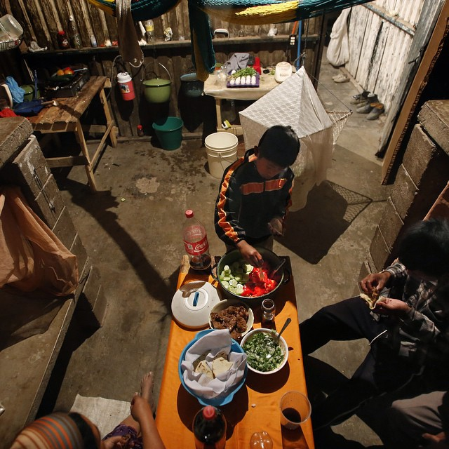 "Family at dinner in a squalid 12x12' labor camp that includes tomatoes and cucumbers scavenged from a modern green house in Sinaloa, Mex.  They pick veggies for your SoCal market. ""Product of Mexico"" continues in LATimes.com (see bio) #mexico #food #veggies #productofmexico #mexican #news #investigative #documentary #doc #storytelling"